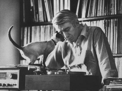 Poet Rod McKuen Playing Record on Stereo Set While Pet Siamese Cat Nuzzles His Face Affectionately