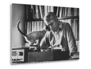Poet Rod McKuen Playing Record on Stereo Set While Pet Siamese Cat Nuzzles His Face Affectionately by Ralph Crane