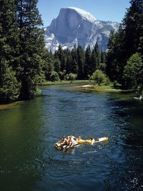 Tourists Float on a Raft in the Merced River at Yosemite National Park by Ralph Crane