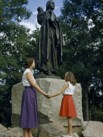 Mother and Daughter Holding Hands Stand Beside Statue of Sacagawea