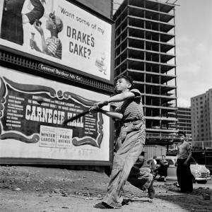 """Boys Playing Stickball in Vacant Lot Next to Drake's Cake and Movie """"Carnegie Hall"""" by Ralph Morse"""