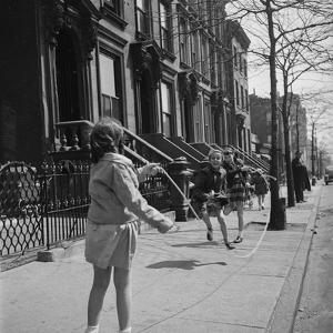 Children Jump Roping on Sidewalk Next to Brooklyn Brownstones, NY, 1949 by Ralph Morse