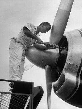 Eastern Airline Employees Working on the Maintaining an Aircraft's Engine by Ralph Morse