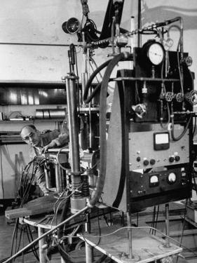 Italian Physicist Enrico Fermi Peering Out from Behind Large, Complicated Machinery in Laboratory by Ralph Morse