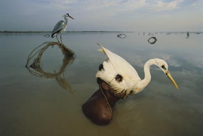 A hunter near Mohenjo Caro, Pakistan, uses an egret headdress as a decoy to stalk birds by Randy Olson