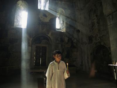 An Altar Boy Holds a Candle Inside a Dimly-Lit Church by Randy Olson