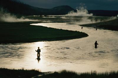 Silhouetted men fish in the Firehole River surrounded by geothermal activity. by Randy Olson