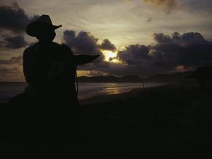 A Cowboy on His Horse Enjoys Sunrise on a Beach by Raul Touzon