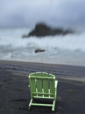 A Green Lounge Chair on a Black Sand Beach by Raul Touzon