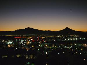 A Night View of Sprawling Mexico City and Nearby Mountains by Raul Touzon