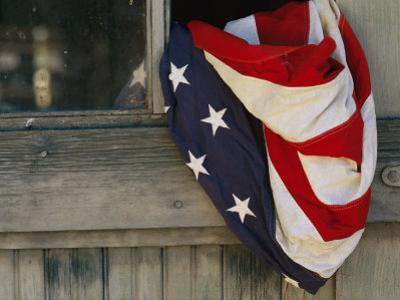 An American Flag Draped Through an Open Barn Window by Raul Touzon