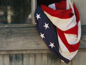 An American Flag Draped Through an Open Barn Window by Raul Touzon