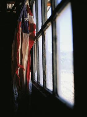 An American Flag Hangs in a Window by Raul Touzon