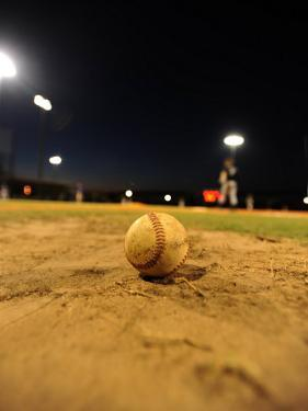 Baseball on a Dirt Mound During a Night Game by Raul Touzon