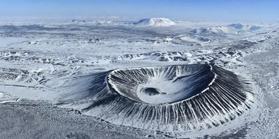 Circular Hverfjall volcano crater covered in snow near Lake Myvatn. by Raul Touzon