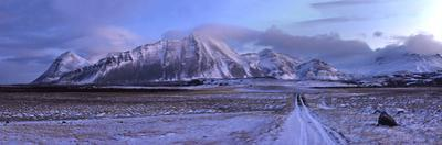 Panorama Image of Mountain Range Covered in Snow at Sunrise by Raul Touzon