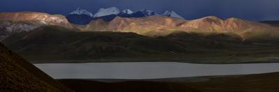 Panorama views of snow-capped mountains with rain clouds in the Eduardo Avaroa Reserve. by Raul Touzon