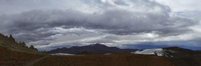 Snowcapped mountains with rain clouds in the Eduardo Avaroa Reserve in Bolivia. by Raul Touzon
