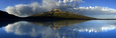 Tunupa volcano reflected on the Uyuni Salt Flats at sunset in Bolivia. by Raul Touzon