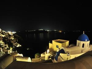Whitewashed Buildings in Oia at Night by Raul Touzon