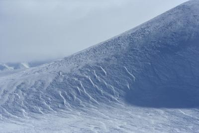 Windswept snow on a mountain slope. by Raul Touzon