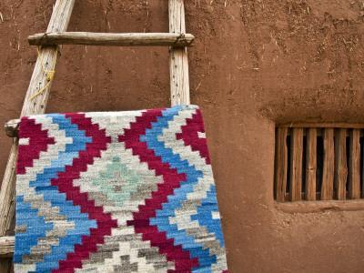 Woven Mat with Native American Indian Motif Against Mud-Brick Wall