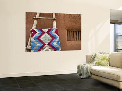 Woven Mat with Native American Indian Motif Against Mud-Brick Wall by Ray Laskowitz