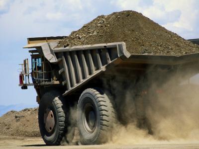 A Dump Truck Carrying Gravel Kicks up a Cloud of Dust by Raymond Gehman