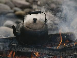 A Kettle of Water Comes to a Boil over a Smoky Campfire by Raymond Gehman