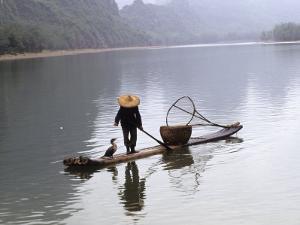 Cormorant Fisherman on Bamboo Raft, Li River, Guilin, Guangxi, China by Raymond Gehman