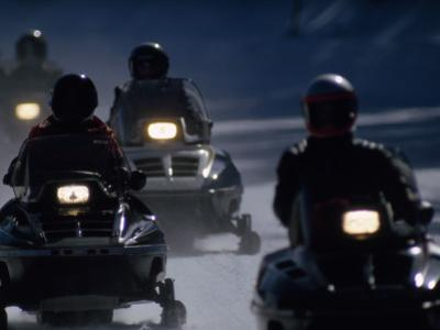 Snowmobilers Ride Down a Snowy Road in Yellowstone Park