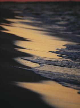 Surf Gently Lapping on a Sandy Beach at Twilight by Raymond Gehman
