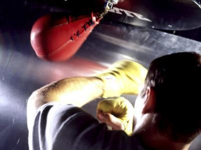 Rear View of a Boxer Punching a Punching Bag