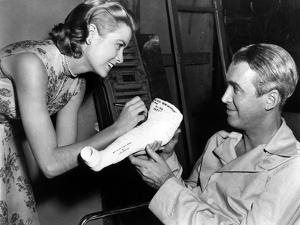 REAR WINDOW, 1954 directed byALFRED HITCHCOCK On the set, Grace Kelly and James Stewart (b/w photo)