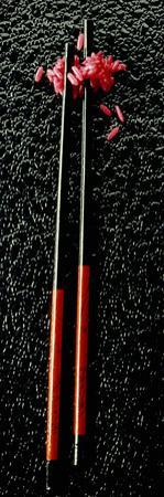 Red Rice with Chopsticks on Black Background