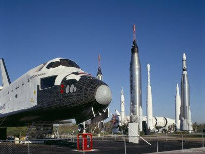 https://imgc.allpostersimages.com/img/posters/retired-shuttle-and-rockets-kennedy-space-center-florida-usa_u-L-P1TCH90.jpg?p=0