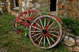 Old Wagon Wheels Lean Against a Stone Building by Rex A. Stucky