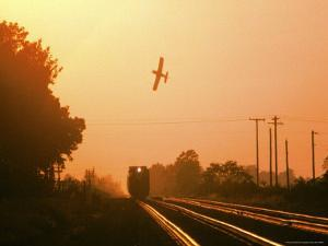 Aerial Crop Duster and Train at Sunrise by Rex Stucky