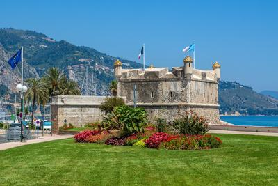 Green Grass with Flowers on Promenade and Medieval Fortress in Menton, France.