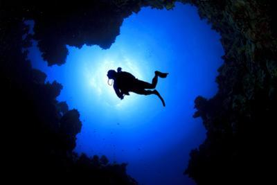 Scuba Diver Swims over Underwater Cave, Silhouette against Sun by Rich Carey