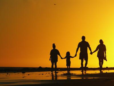 A Family Holding Hands is Silhouetted against the Setting Sun