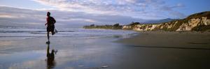 A Man Jogs Along Sands Beach Below Ellwood Bluffs, at Sunset by Rich Reid