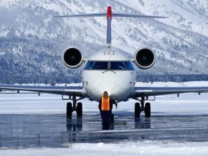 Aircraft at Jackson Hole Airport Surrounded by Snow-Covered Fields and Hills, Jackson Hole, Wyoming by Richard Cummins