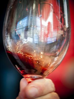 USA, Oregon, Portland. A swirl of red wine in glass reflecting light. by Richard Duval