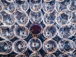USA, Washington State, Seattle. One glass of red wine in a row of wine glasses. by Richard Duval