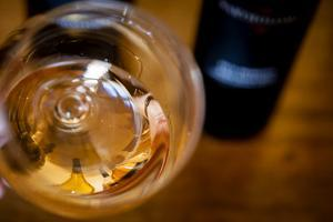 USA, Washington State, Seattle. Wine bottles are reflected in a glass of L'Orange, a Pinot Gris mad by Richard Duval