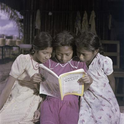 Three Sisters Look at a Copy of National Geographic Magazine by Richard Hewitt Stewart
