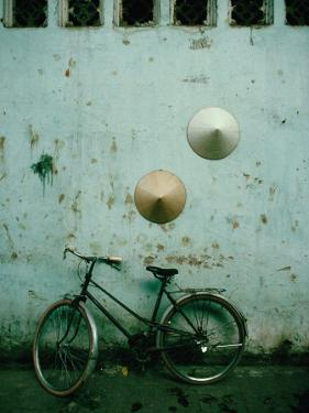 Conical Hats Hang on Wall Above Bicycle in Historic Old Quarter, Hanoi, Vietnam by Richard I'Anson