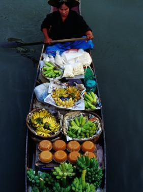 Woman Paddling Wooden Canoe Laden with Fruit for Sale at Floating Market, Damnoen Saduak, Thailand by Richard I'Anson
