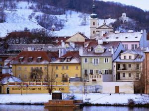 Snow-Covered Houses on Kampa Island on Banks of Vltava River, Prague, Czech Republic by Richard Nebesky